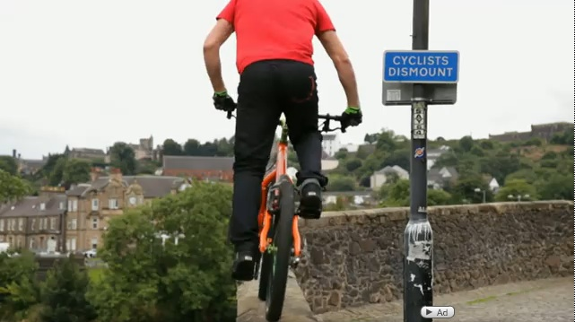 Sign reading 'Cyclists dismount,' right before MacAskill jumps off the bridge.
